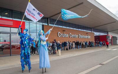 Stelzenkünstler mit Willkommensgruß: Nordwindbraut und Aquarius empfangen erste Kreuzfahrtgäste in Steinwerder